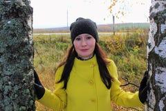 Tiempo del otoño: muchacha hermosa en una capa amarilla que presenta contra un bosque otoñal del abedul Imagenes de archivo