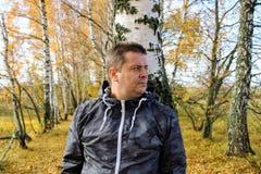 Tiempo del otoño: un hombre en los tejanos que presentan contra el contexto de un bosque del abedul del otoño Imagen de archivo libre de regalías