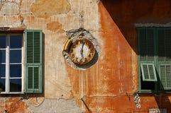 Tiempo del simbolismo: reloj del vintage en una pared lamentable Foto de archivo libre de regalías