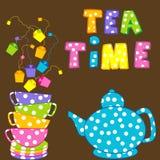 Tiempo del té con las tazas y la caldera apiladas Imágenes de archivo libres de regalías