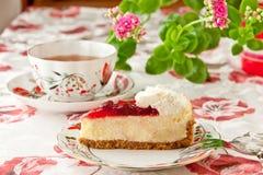 Tiempo del té. Pastel de queso de la fresa y taza de té. Fotografía de archivo