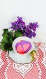 Tiempo del té - platee el platillo arreglado y la taza de té llenados de los corazones del papel del recorte witting en tapetito  Imagenes de archivo