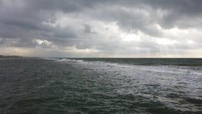 Tiempo dramático sobre las ondas que amenazan del mar que se estrellan en la orilla con el cielo y los rayos de sol cubiertos en  metrajes