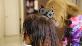 Tiempo en un salón de belleza Mujer joven en un salón de belleza, peluquero que hace el peinado al modelo hermoso almacen de video