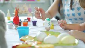 Tiempo feliz mientras que pinta los huevos de Pascua almacen de metraje de vídeo