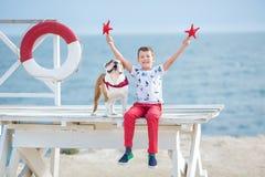 Tiempo happyly de gasto adolescente del muchacho hermoso así como su dogo del amigo en el perro del niño del lado de mar que llev Fotos de archivo