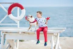 Tiempo happyly de gasto adolescente del muchacho hermoso así como su dogo del amigo en el perro del niño del lado de mar que llev Imagen de archivo libre de regalías