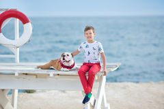 Tiempo happyly de gasto adolescente del muchacho hermoso así como su dogo del amigo en el perro del niño del lado de mar que llev Fotos de archivo libres de regalías