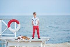 Tiempo happyly de gasto adolescente del muchacho hermoso así como su dogo del amigo en el perro del niño del lado de mar que llev Imagen de archivo