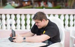 Tiempo libre enloying adolescente joven mirando su pequeño ordenador Imagen de archivo libre de regalías
