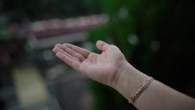 Tiempo lluvioso, gotas de lluvia que bajan en la mano de la mujer La lluvia est? cayendo en una mano del ` s del hombre almacen de metraje de vídeo