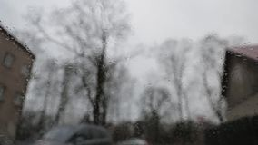 Tiempo melancólico lluvioso visto desde adentro de un coche con los limpiadores que quitan activamente gotas de lluvia del parabr almacen de video