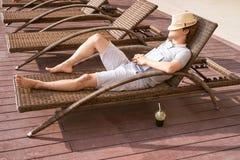 Tiempo perezoso Individuo asiático que duerme en la piscina del sofá en el summ foto de archivo libre de regalías