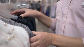 Tiempo que hace compras, ropa elegante selecta de la muchacha de los clientes nueva en suspensiones en tienda de la moda durante  almacen de video