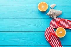 Tiempo y chancletas de la diversión del verano Shell del mar Deslizadores y fruta anaranjada en fondo de madera azul Mofa ascende imagenes de archivo
