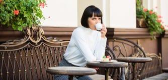 Tiempo y relajación agradables Bocado delicioso y gastrónomo La muchacha relaja el café con café y el postre Concepto del postre imagen de archivo