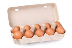 Tien bruine eieren in een kartonpakket Stock Fotografie