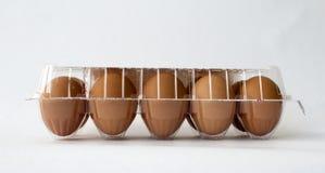 Tien bruine kippeneieren in plastic containerpakket Stock Fotografie
