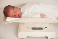 Tien dagen oude nieuw - geboren kind op schaal die gewicht meten royalty-vrije stock foto's