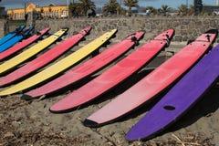 Tien die beginnersurfplanken op het strand worden opgesteld Stock Foto