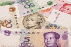 Tien die dollarrekening door Chinese Yuans wordt omringd Stock Fotografie