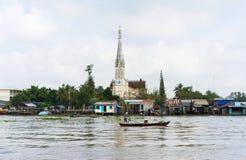 Tien Giang,越南- 2014年11月28日:连队在湄公河三角洲的河场面,与划艇和教会背景的 免版税库存照片