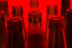 Tien groene lege die bierflessen met rood licht worden geschoten royalty-vrije stock foto's