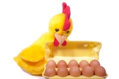 Tien kippeneieren in gele doos met stuk speelgoed haan (witte backgroun Stock Afbeelding