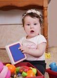 Tien maanden babymeisje het spelen met boek Stock Afbeelding