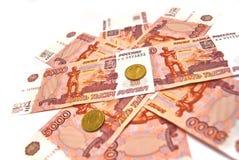 Tien roebelsmuntstukken en vijf duizend bankbiljetten Stock Afbeeldingen