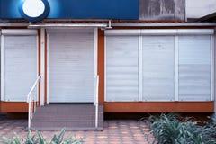 Tienda abandonada con las cortinas cerradas del metal foto de archivo