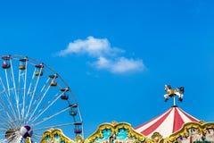 Tienda antigua de los caballos del carrusel en parque de atracciones con la noria colorida Foto de archivo