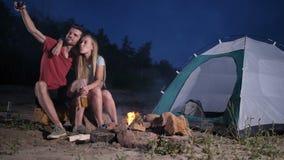 Tienda de amor de los pares que acampa en la playa que toma el selfie metrajes