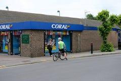 Tienda de apuesta británica bien conocida vista así como un ciclista inmóvil en el primero plano, mirando a través de su ventana foto de archivo libre de regalías