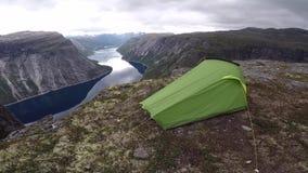 Tienda de campaña en el sitio para acampar salvaje escénico al borde del fiordo noruego almacen de video