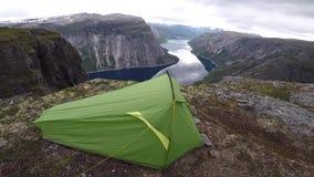 Tienda de campaña en el sitio para acampar salvaje escénico al borde del fiordo noruego metrajes