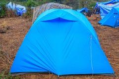 Tienda de campaña en la hierba seca cerca de la montaña por la mañana imagen de archivo