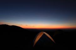 Tienda de campaña en la puesta del sol imagenes de archivo