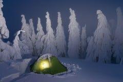 Tienda de campaña verde que brilla intensamente en montañas de la nieve en el bosque del invierno en un cuento de hadas Viaje a t foto de archivo