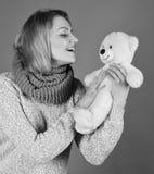 Tienda de juguete o tienda del juguete Concepto infantil del humor La mujer sostiene el oso de peluche Imagen de archivo