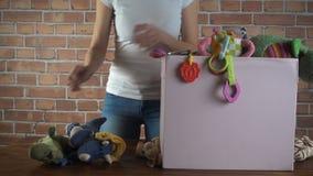 Tienda de la caridad Mujer que clasifica los juguetes usados que le donaron, vídeo de la cámara lenta almacen de video