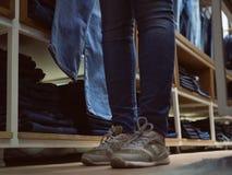 Tienda de la ropa de los vaqueros Muchacha de las piernas en vaqueros en stor de la ropa del dril de algodón Fotografía de archivo libre de regalías
