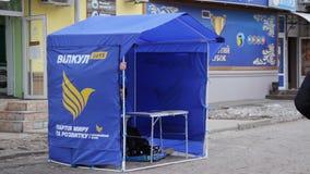 Tienda de los promotores de la calle con los materiales de los medios de la campaña que hacen publicidad del candidato para el pr