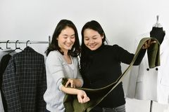 Tienda de ropa, dise?ador de moda asi?tico que trabaja en su estudio de la sala de exposici?n, modista que hace juego el mejor co imagen de archivo
