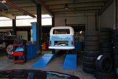Tienda del coche del vintage con los coches en la reparación Foto de archivo