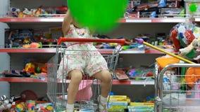 Tienda del ` s de los niños con los juguetes Un niño en un supermercado se sienta en el carro de la compra almacen de metraje de vídeo