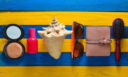 Tienda los accesorios para la relajación en la playa y la belleza en una tabla de madera azul amarilla Frunza, botella de perfume Imagenes de archivo