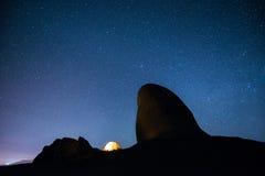 Tienda que brilla intensamente en las montañas debajo de un cielo estrellado Imagenes de archivo