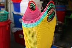 Tienda que vende las cestas plásticas rosa, tiendas verdes, amarillas de la pequeña empresa en el mercado asiático imagen de archivo libre de regalías
