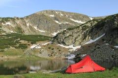 Tienda roja del caminante cerca del lago de la montaña Fotos de archivo